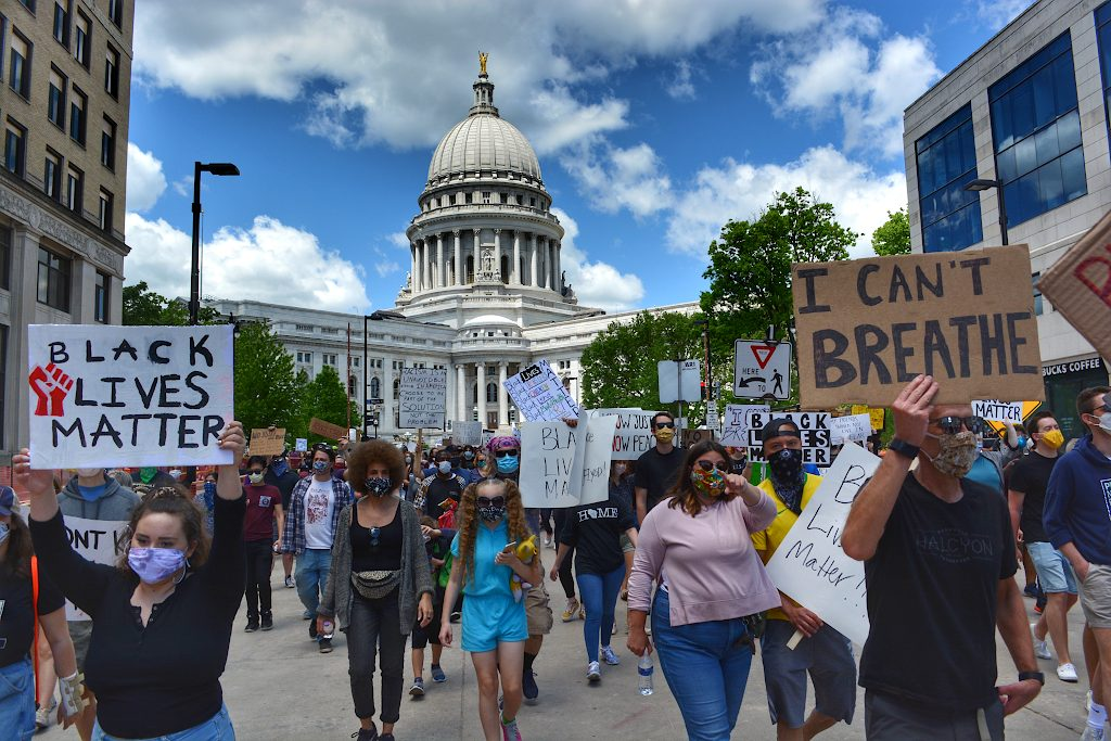 Protestors march away from the Capitol, with signs saying Black Lives Matter and I Can't Breathe