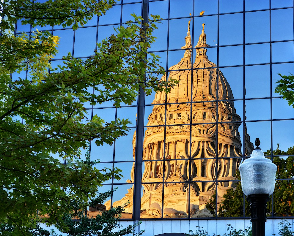Wisconsin State Capitol reflected in a glass building with a tree and lamppost on either side