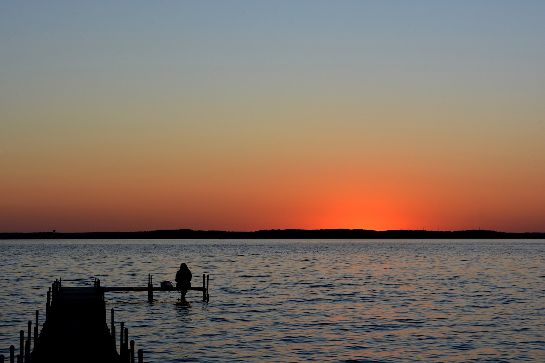 Glowing sunset sky over a lake with a silhouette of a person sitting on a pier