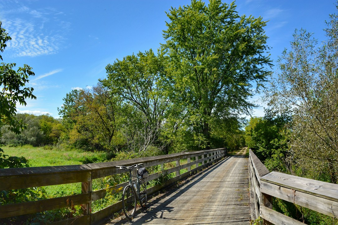 bicycle parked on a brige of a recreational trail with trees in the background