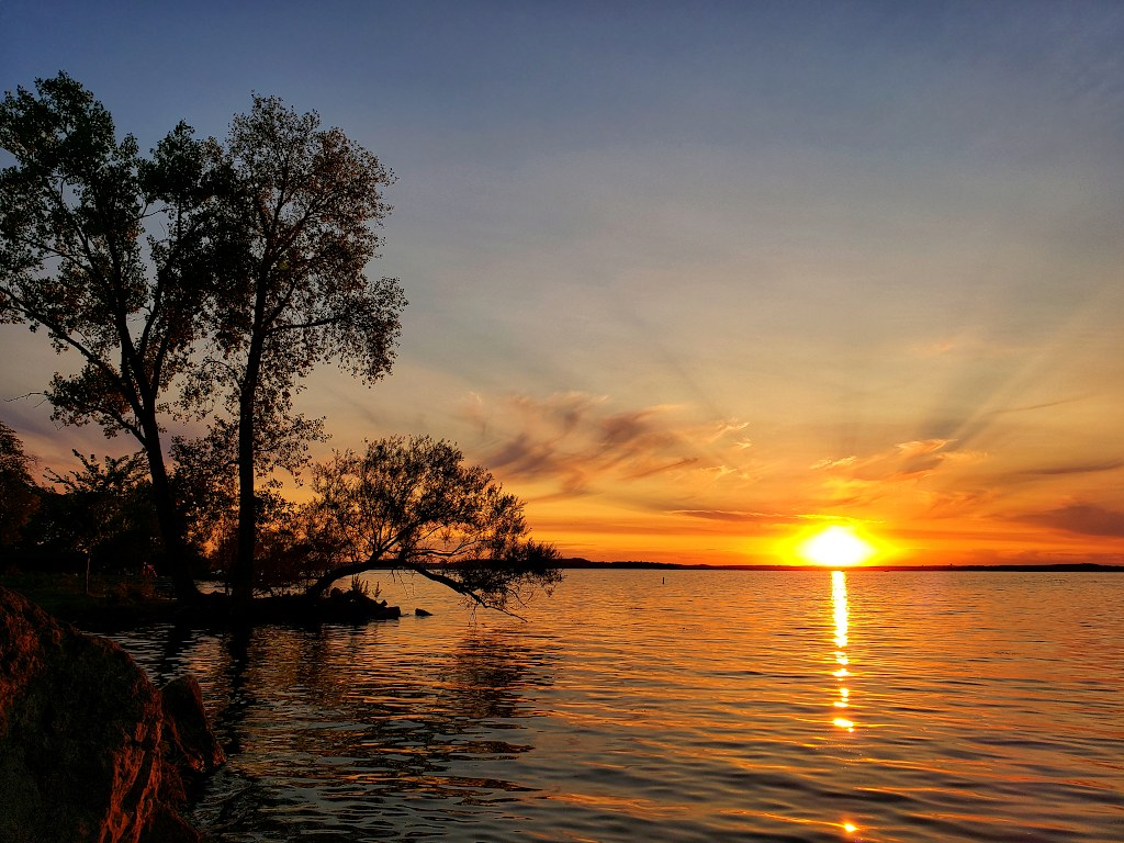 Sun just above the horizon, creating a colorful sky over a lake, with trees on the side in silhouette