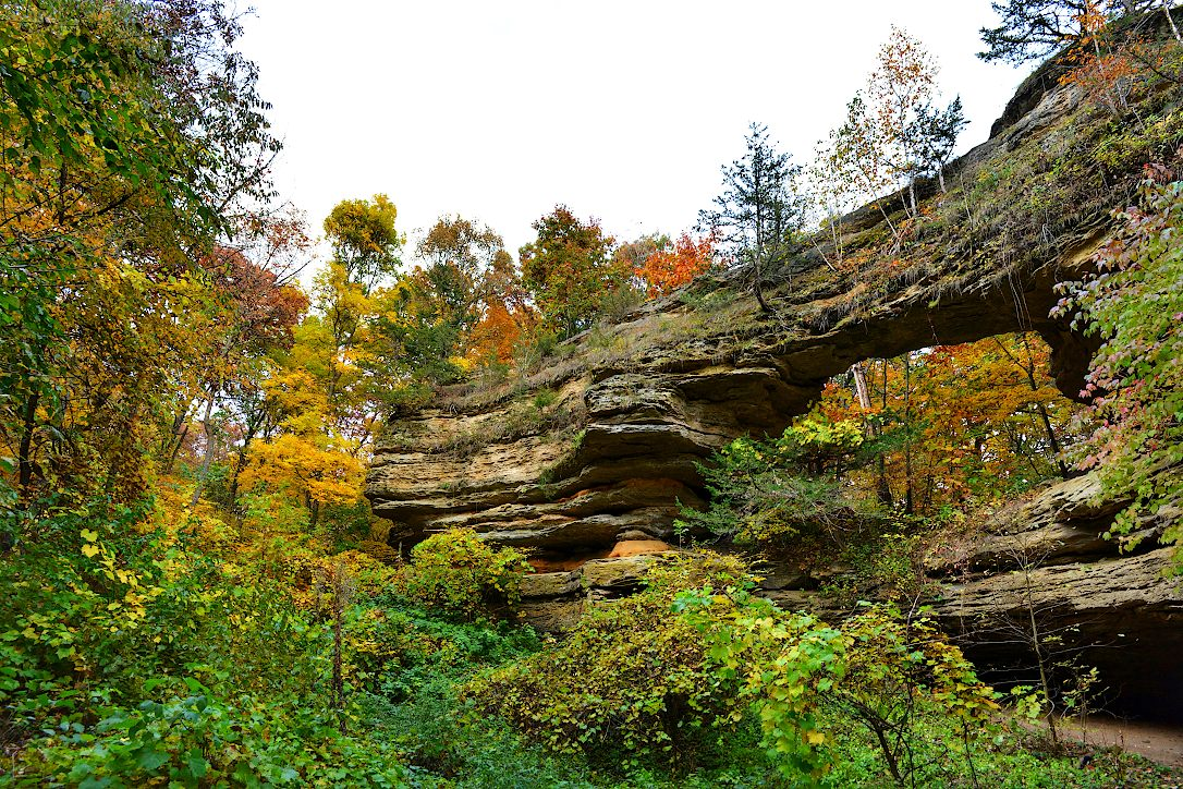 Natural sandstone arch surrounded by trees turning autumn colors