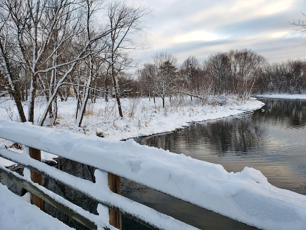 Snow covered bridge railing over a creek with a snowy landscape in the background