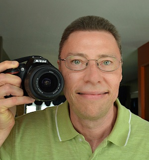 Jonathan Bloy holding a camera taking a self portrait