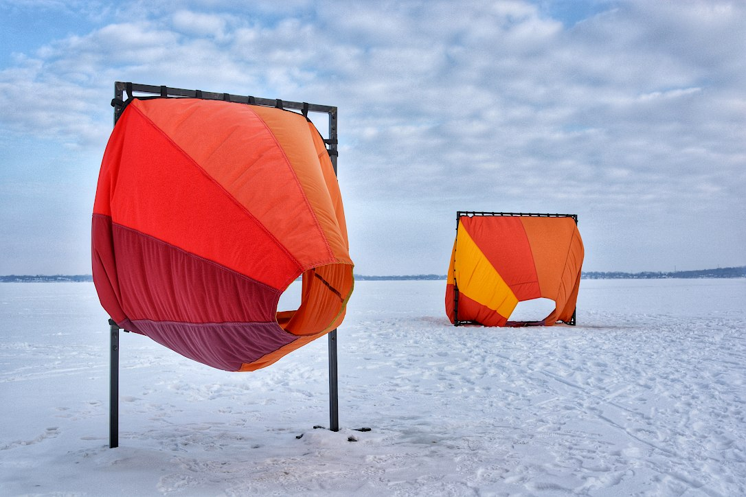 Two large multi colored wind socks blowing in the breeze, mounted in frames set in a frozen covered lake