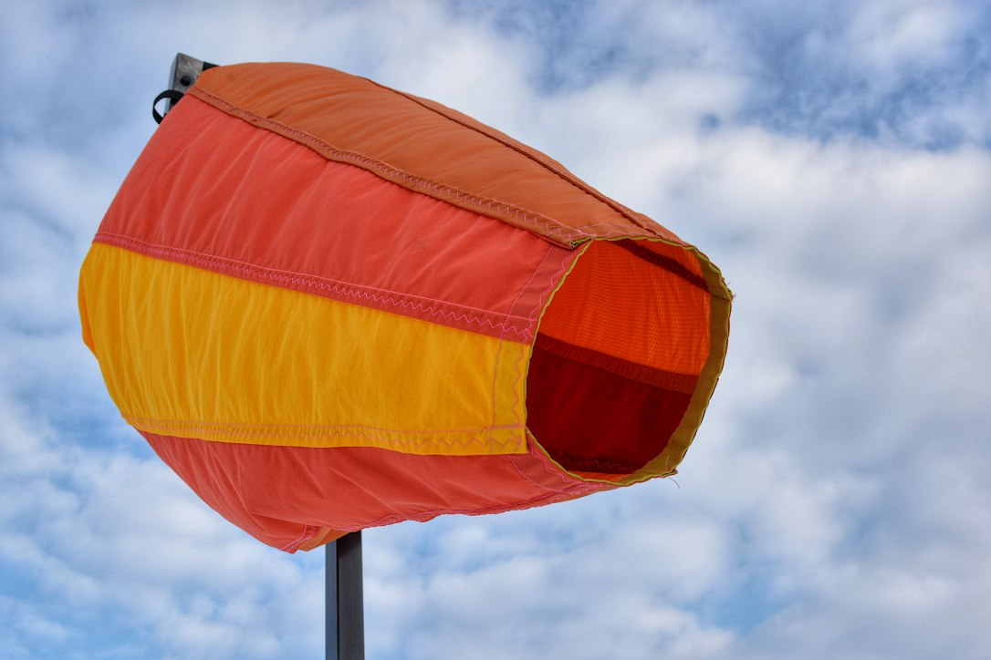 Close up of a large red, yellow, and orange wind sock blowing in the breeze.