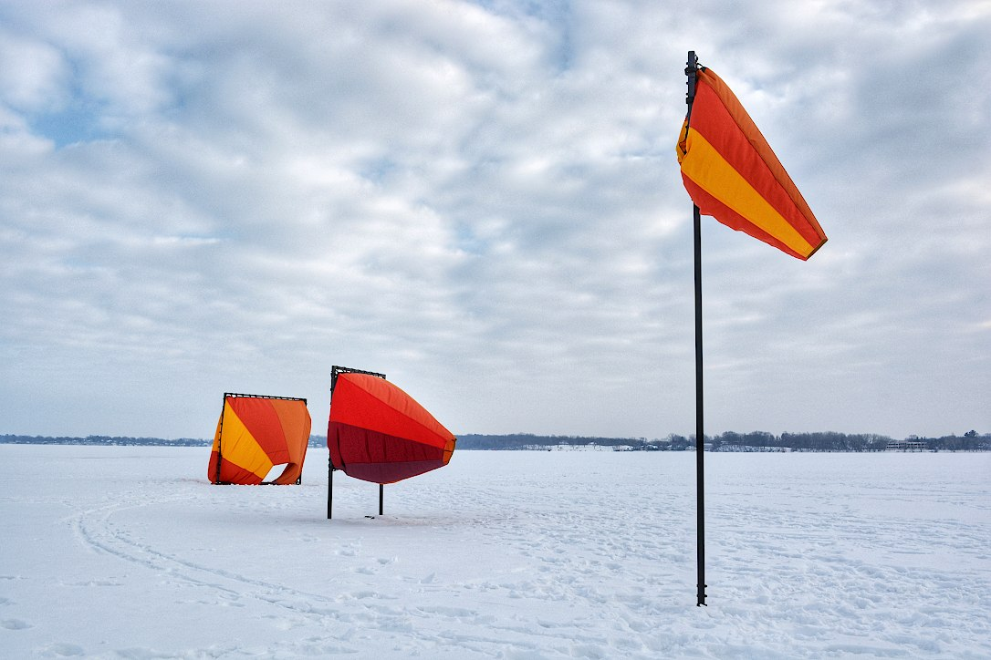 Three colorful windsocks of different sizes, mounted on a frozen and snow covered lake, blowing in the breeze.