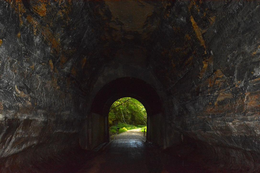 Inside a dark tunnel with a distant opening showing green trees and sunlight