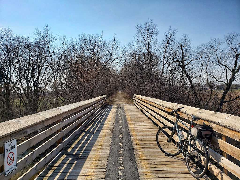 Bicycle parked on a wooden bridge with bare trees in the background and a trail leading off into the distance